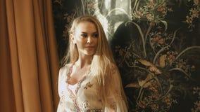 Mooi blonde met lang haar in een kleding in modieuze intreire stock videobeelden