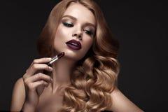 Mooi blonde op een Hollywood-manier met krullen, donkere lippen, lippenstift ter beschikking Het gezicht en het haar van de schoo stock afbeelding