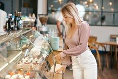 Mooi blondemeisje die dessert kiezen van glasshowcase in bakkerijwinkel royalty-vrije stock foto