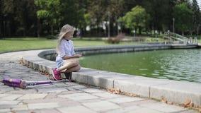 Mooi blondemeisje die dichtbij het meer in het park rusten stock video
