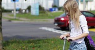 Mooi blondemeisje die een autoped in de stad berijden stock footage