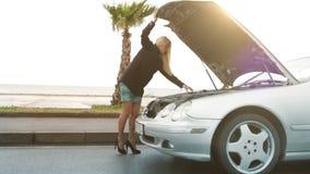 Mooi blondemeisje die iets onder de kap van haar gebroken auto kijken stock video