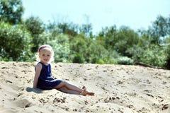 Mooi blondemeisje die op strand rusten Stock Foto's