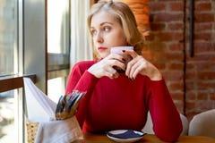 Mooi blondemeisje die uit het venster, die een Kop van koffie houden kijken Peinzende vrouw die over aanstaande gevallen denken stock afbeeldingen
