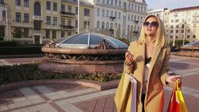 Mooi blondemeisje die in zonnebril met het winkelen zakken in een stad lopen stock videobeelden