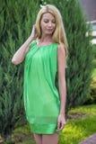 Mooi blondemeisje in een groene korte de zomerkleding op de straten van de stad Stock Afbeeldingen