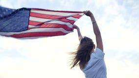 Mooi blondemeisje en Amerikaanse vlag stock footage