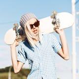 Mooi blondemeisje in korte borrels met skateboard Royalty-vrije Stock Foto's