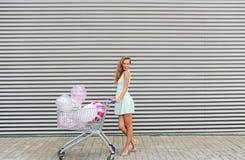 Mooi blondemeisje met golvend haar lopend en rollend boodschappenwagentje met kleurenballons Stock Afbeelding