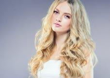 Mooi blondemeisje met lang krullend haar over purpere backgroun royalty-vrije stock fotografie