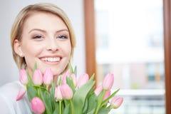 Mooi blondemeisje met tulpen stock foto