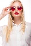 Mooi blondemeisje in roze glazen en overhemd Het Gezicht van de schoonheid Geïsoleerdj op witte achtergrond royalty-vrije stock afbeeldingen