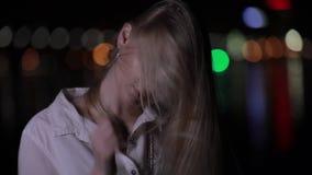 Mooi blondemodel met het lange haar stellen in nachtstad stock video