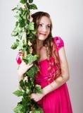 Mooi blondy meisje die in rode kleding op de groene wijnstokdruiven houden Stock Afbeeldingen