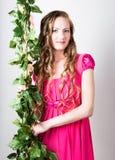 Mooi blondy meisje die in rode kleding op de groene wijnstokdruiven houden Stock Afbeelding