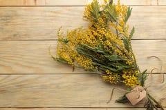 Mooi boeket van gele mimosabloemen op een natuurlijke houten lijst Hoogste mening Vrije ruimte Ruimte voor tekst stock foto