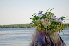 Mooi boeket van kroon van wilde bloemen op het hoofd van een meisje dichtbij de waterrivier stock afbeelding