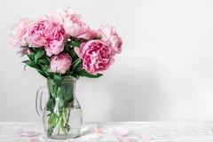 Mooi boeket van roze pioenbloemen in vaas de dag van de vrouw of huwelijksachtergrond met exemplaarruimte stock foto