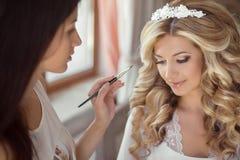 Mooi bruidhuwelijk met make-up en kapsel De stilist maakt stock foto's