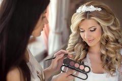 Mooi bruidhuwelijk met make-up en kapsel De stilist maakt royalty-vrije stock afbeeldingen