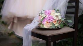 Mooi bruids boeket op de lijst met mooie huwelijkskleding en bruids toebehoren op de achtergrond Huwelijk stock video