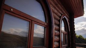Mooi bruin die blokhuis van logboeken wordt gemaakt Bezinning van de hemel in de vensters van het huis stock video
