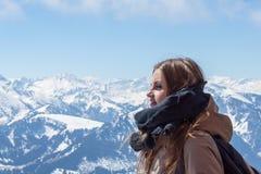 Mooi bruin-haired meisje op het terras van een chalet in het hooggebergte Een jong meisje en een de zomerdag in de bergen stock afbeelding
