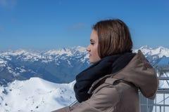 Mooi bruin-haired meisje op het terras van een chalet in het hooggebergte Een jong meisje en een de zomerdag in de bergen stock fotografie