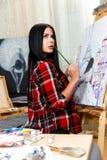 Mooi brunette belast met het schilderen Stock Afbeeldingen