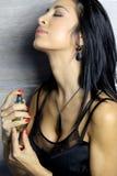 Mooi brunette dat een parfum gebruikt Stock Foto's