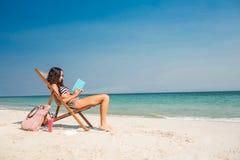 Mooi brunette die een boek op ligstoel lezen stock foto