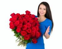 Mooi brunette die een groot boeket van rode ros houden stock foto