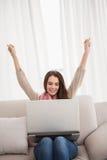 Mooi brunette die gebruikend laptop toejuichen Stock Afbeeldingen