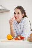 Mooi brunette die gesneden peper eten Royalty-vrije Stock Afbeeldingen