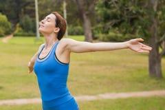 Mooi brunette die haar wapens uitrekken tijdens jogging Royalty-vrije Stock Fotografie