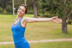 Mooi brunette die haar wapens uitrekken tijdens jogging Stock Fotografie