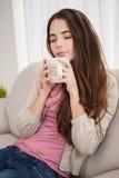Mooi brunette die koffie op de laag hebben Stock Foto
