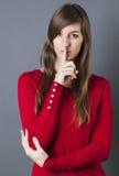 Mooi brunette die lippen houden voor discretie of voorzorgsmaatregel strak stock fotografie