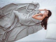 Mooi brunette die op bed thuis liggen Royalty-vrije Stock Foto