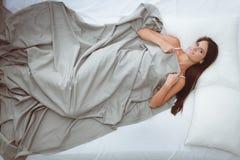 Mooi brunette die op bed thuis liggen Stock Foto