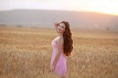 Mooi Brunette die op tarwegebied bij zonsondergang genieten van openlucht zo royalty-vrije stock fotografie