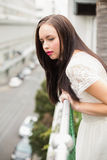Mooi brunette die over het balkon kijken Stock Foto