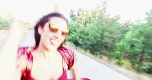 Mooi brunette die terwijl het zitten op gesorteerde kap van convertibel, dansen stock video