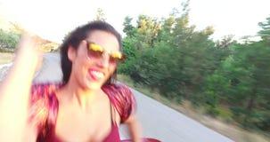Mooi brunette die terwijl het zitten op kap van convertibel dansen stock videobeelden