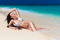 Mooi brunette die van de zon op de tropische kust genieten Stock Afbeelding