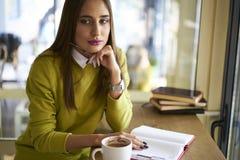Mooi brunette in een gele blouse in agenda voor het creëren van karakters van vreemdelingen buiten het venster Royalty-vrije Stock Foto's