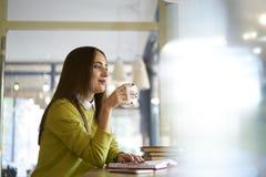 Mooi brunette in een gele blouse die van beste ideeën op vergadering met werknemer nota nemen te bespreken terwijl het genieten v Stock Foto