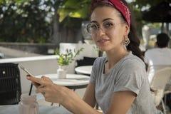 Mooi brunette in een koffie op straat het stellen met telefoon, stock fotografie