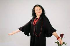 Mooi brunette in een zwarte kleding De rokopwinding In haar hand, houdt een vrouw een rood toenam, heeft zij etnische rode parels Stock Afbeelding