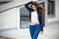 Mooi brunette in leerjasje en jeans Stock Afbeeldingen